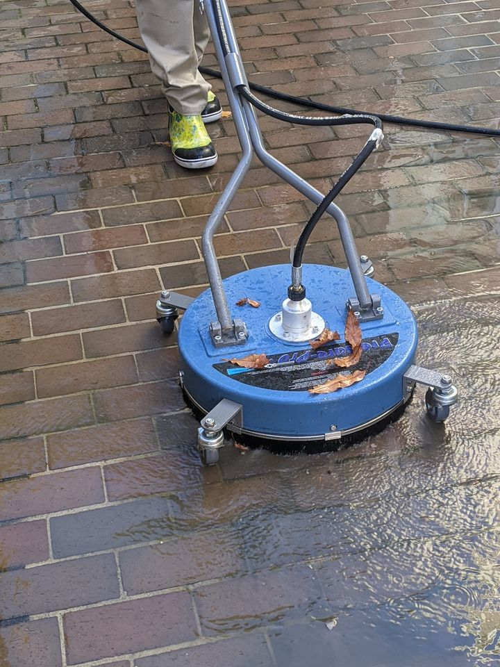 man cleaning brick walkway with a machine