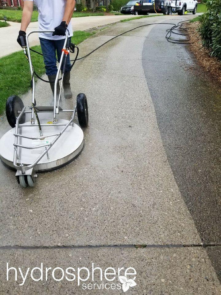 man using machine to clean sidewalk